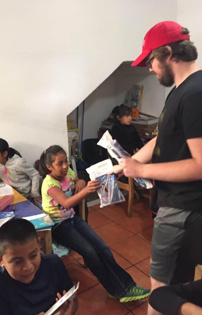 Robert Sullivan hands a dental hygiene kit to a third grader at Escuela Integrada.