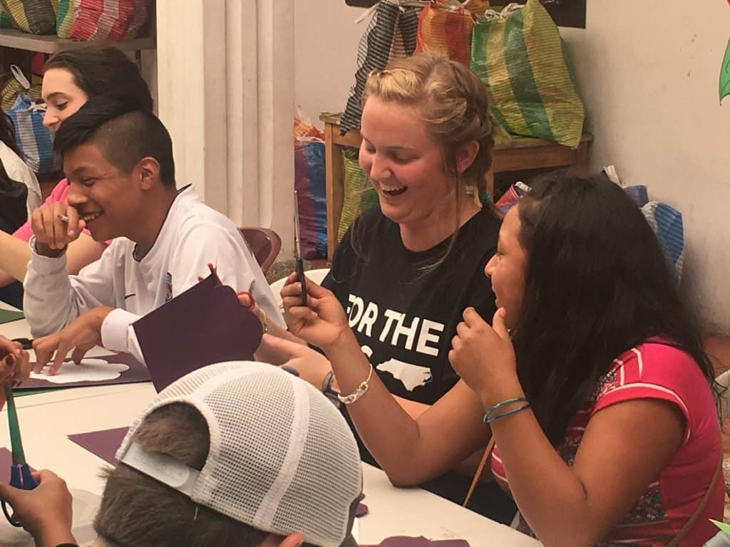 Juliana Anderson works on a craft project with seventh graders at Escuela Integrada.