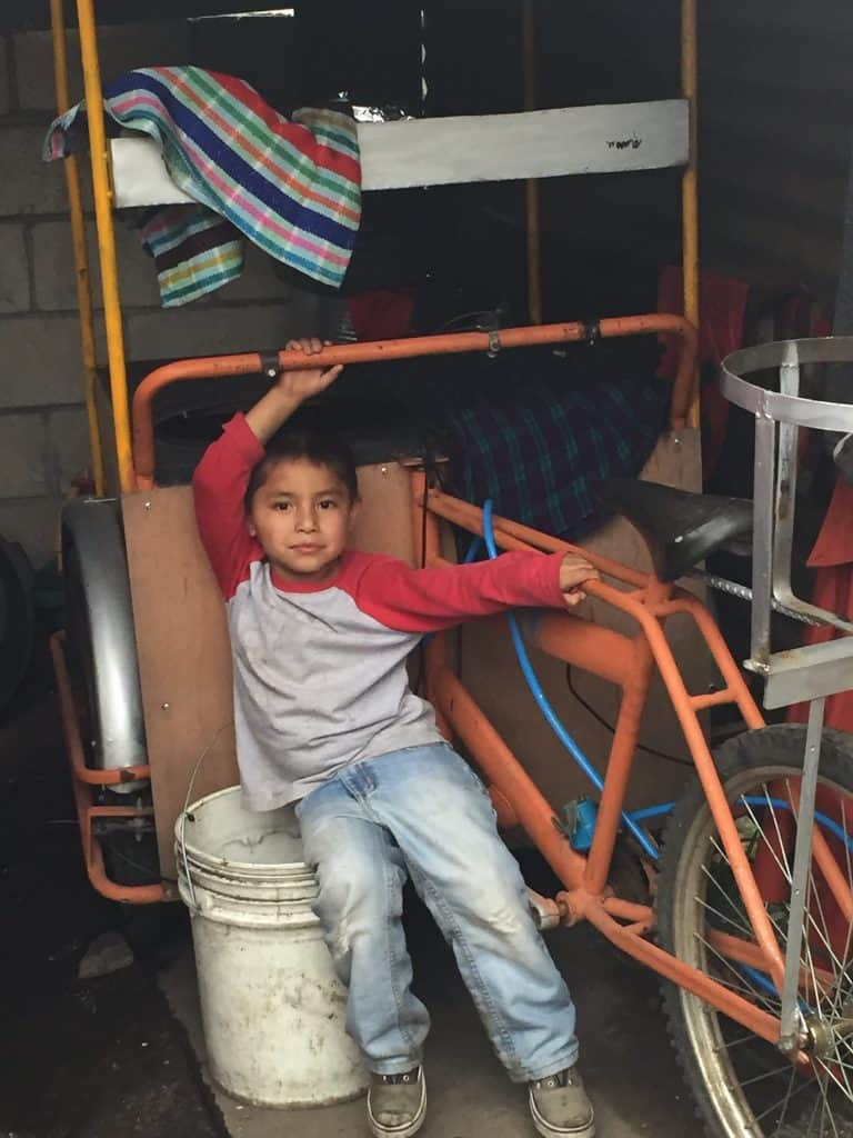Manuel leans against the bicycle cart his mother uses to sell hot food. He rides on his mother's back when she goes into the city.