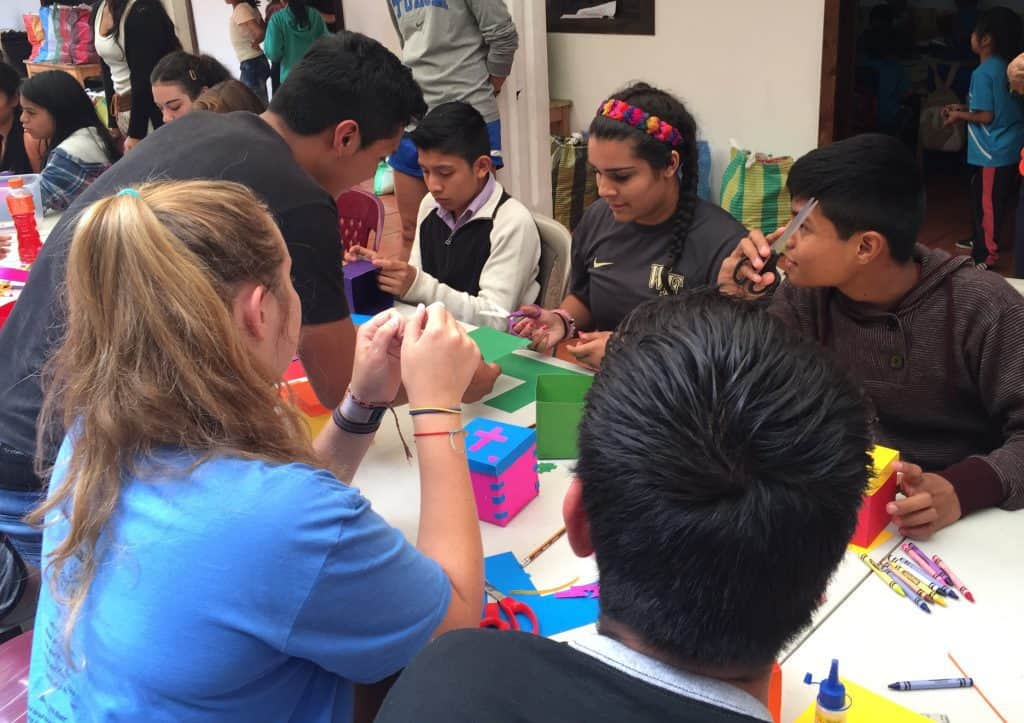 St. John's high schoolers work with Escuela Integrada students on a craft for the residents at Casa Maria in Jocotenango.