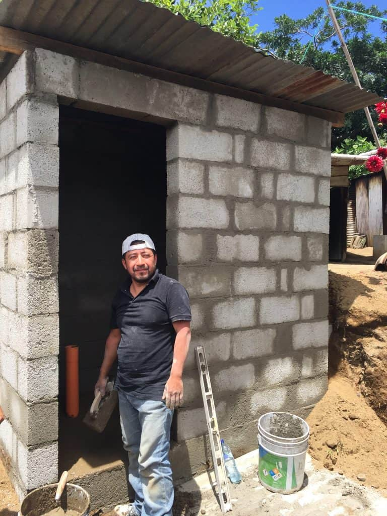 Carlos stands next to the nearly complete bathroom on Friday, Aug. 4, 2017.