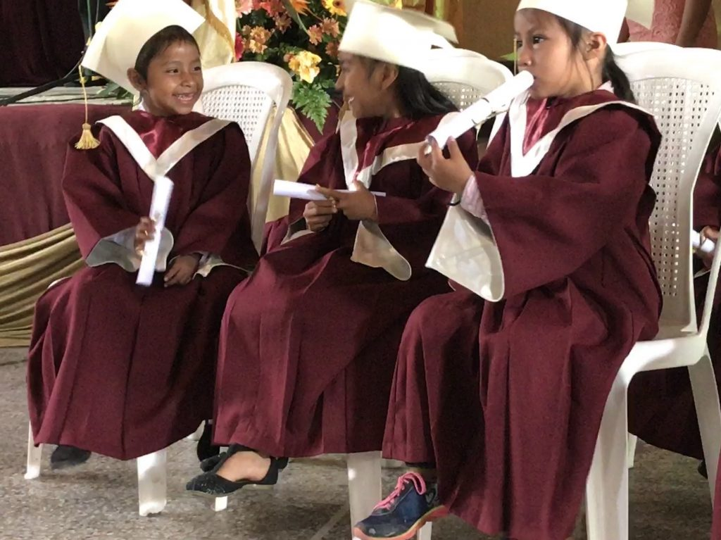 First graders tell secrets and use their diplomas as trumpets at graduation on Nov. 8, 2017.