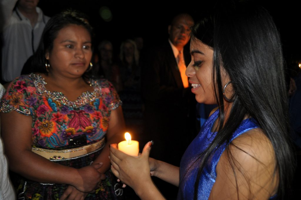 Maria Genoveva presents a candle to her mother during the ceremony in the garden of Hotel Real Plaza.