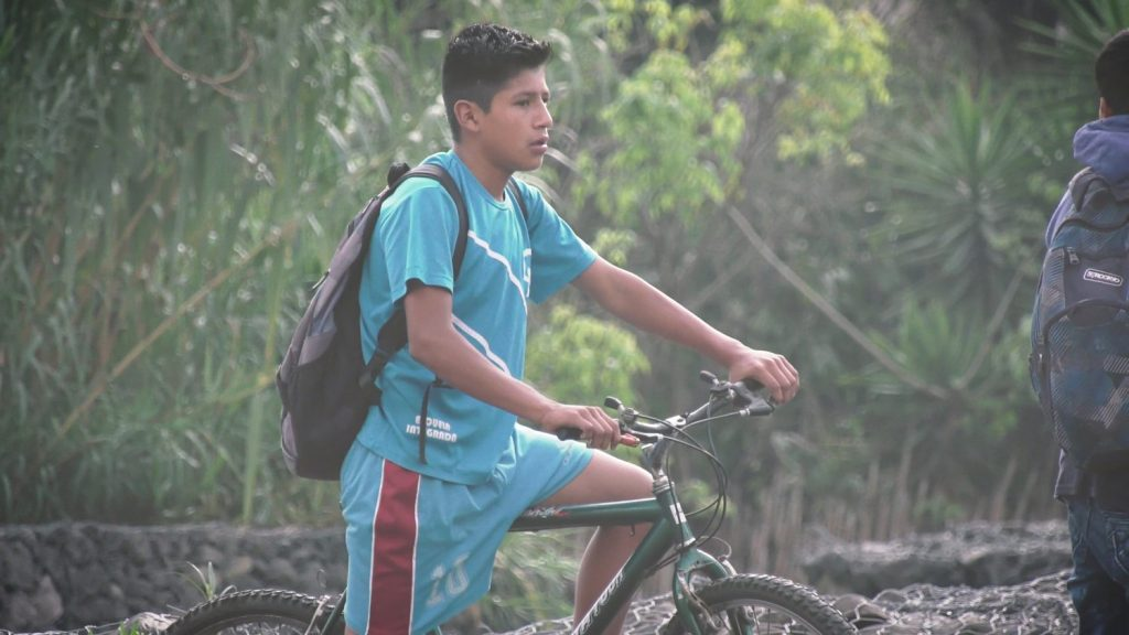 Eli rides his bike 4.6 miles to and from Escuela Integrada. He traverses steep mountainsides and busy streets to get to school each day. The new Escuela Integrada film follows his daily experience.