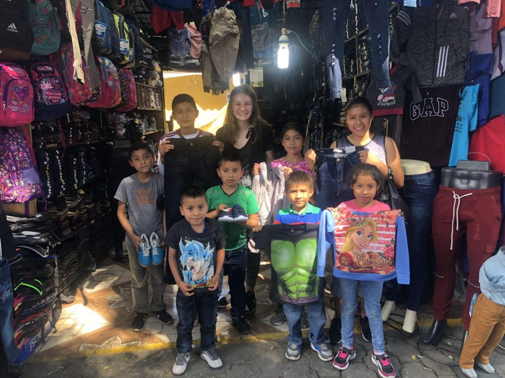 GRACES' intern Breanna Watson stands in front of a store with a group of children from Escuela Integrada.