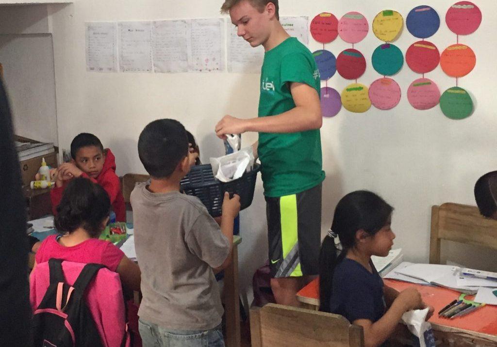 Kevin Agner hands out dental hygiene kits to third graders at Escuela Integrada.