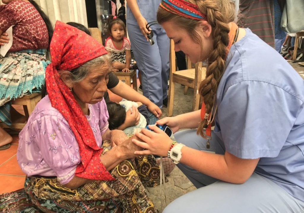 A nurse with International Medical Relief checks the vital signs for a patient at Escuela Integrada on June 25, 2018.