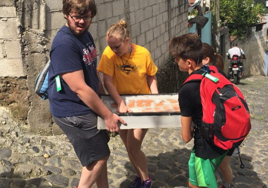 A mission group from St. John's Lutheran Church in Salisbury, North Carolina, carries part of a stove up a hill in San Felipe. The group built a stove for one of the Escuela Integrada families on Wednesday, July 12, 2017.